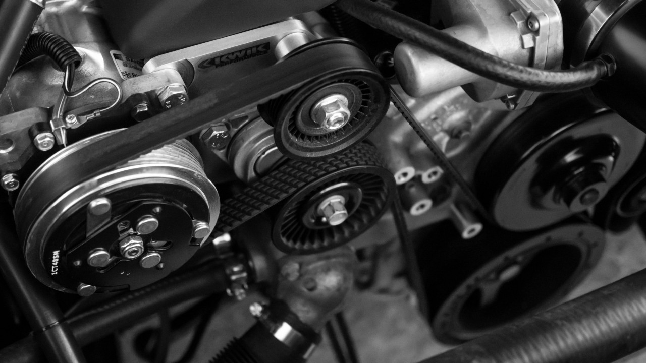 The black and white photograph shows the right part of the engine block of a car from above. We see in a vivid contrast of bright aluminium and black crown wheels and flexible tubes of the same color an assemblage of wheels, transmission belts and brand new srews. Evwrything looks clean and in good shape.