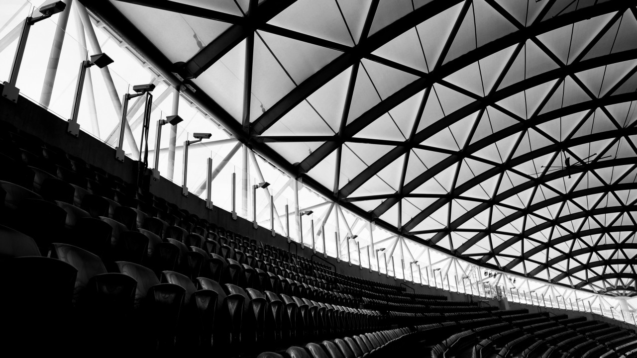 This high contrast black and white photograph shows the left edge of a roofed sports arena. The rhombus shaped roof structure, the small stripe of open space below and the bordering, curved rows of chairs create a mixture of lines and patterns in which a human body would appear misplaced.