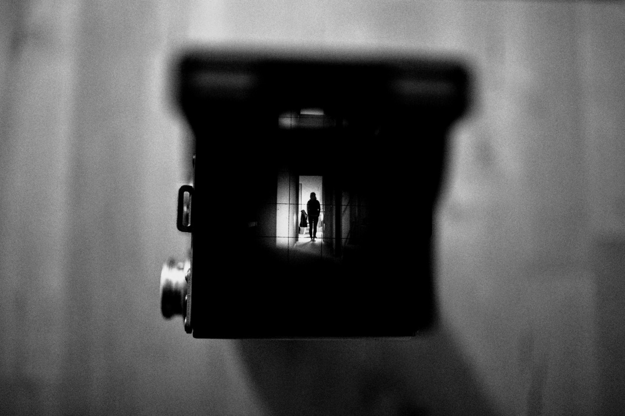 This photograph shows a classic, rectangular photo camera from above. It rests on a blurred wooden table, the focussing screen is open, we can see the thin crosshairs, and in the middle of the nine fields they produce, there is what the camera is seeing: the black, small, elegant figure of a woman standing in the entrance of a room, undecided if to go in. The image is small but very sharp, in contrast with the blurred image of the cam itself and the silvercolored rotary knob on the left of the box.