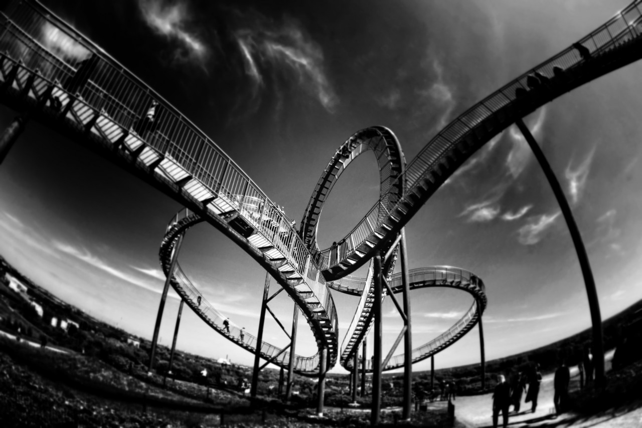"The black and white photograph shows a rollercoaster beginning on the upper left, the tracks following an ""eight"" in the middle and leaving the picture on the upper right. Above a beautiful clear sky with very small, wind driven clouds."
