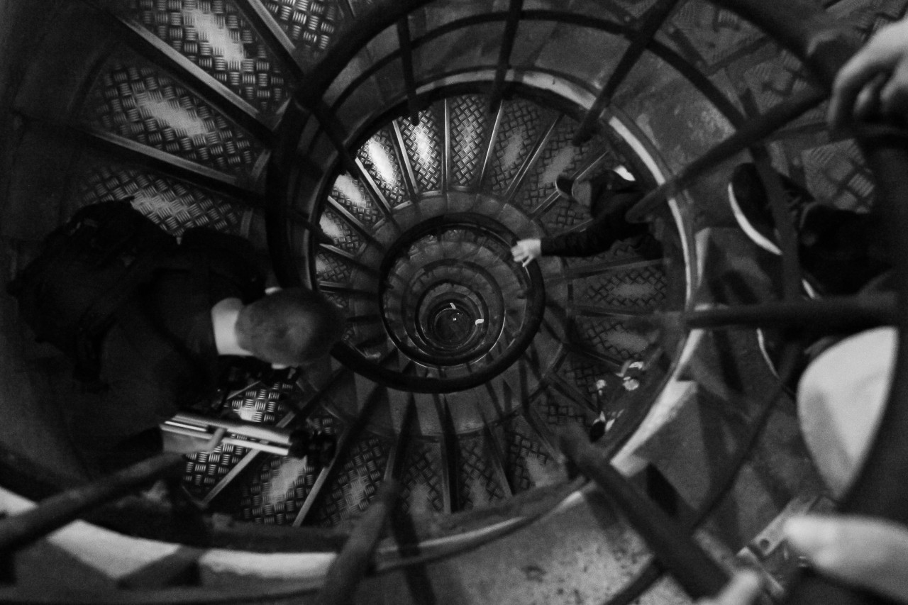 The black and white photograph shows an old fashioned circular stairway with a black iron handrail and three people on different levels. We can't see their faces, one has stopped and is looking downward where we can spot a hand and an arm of a person coming up.